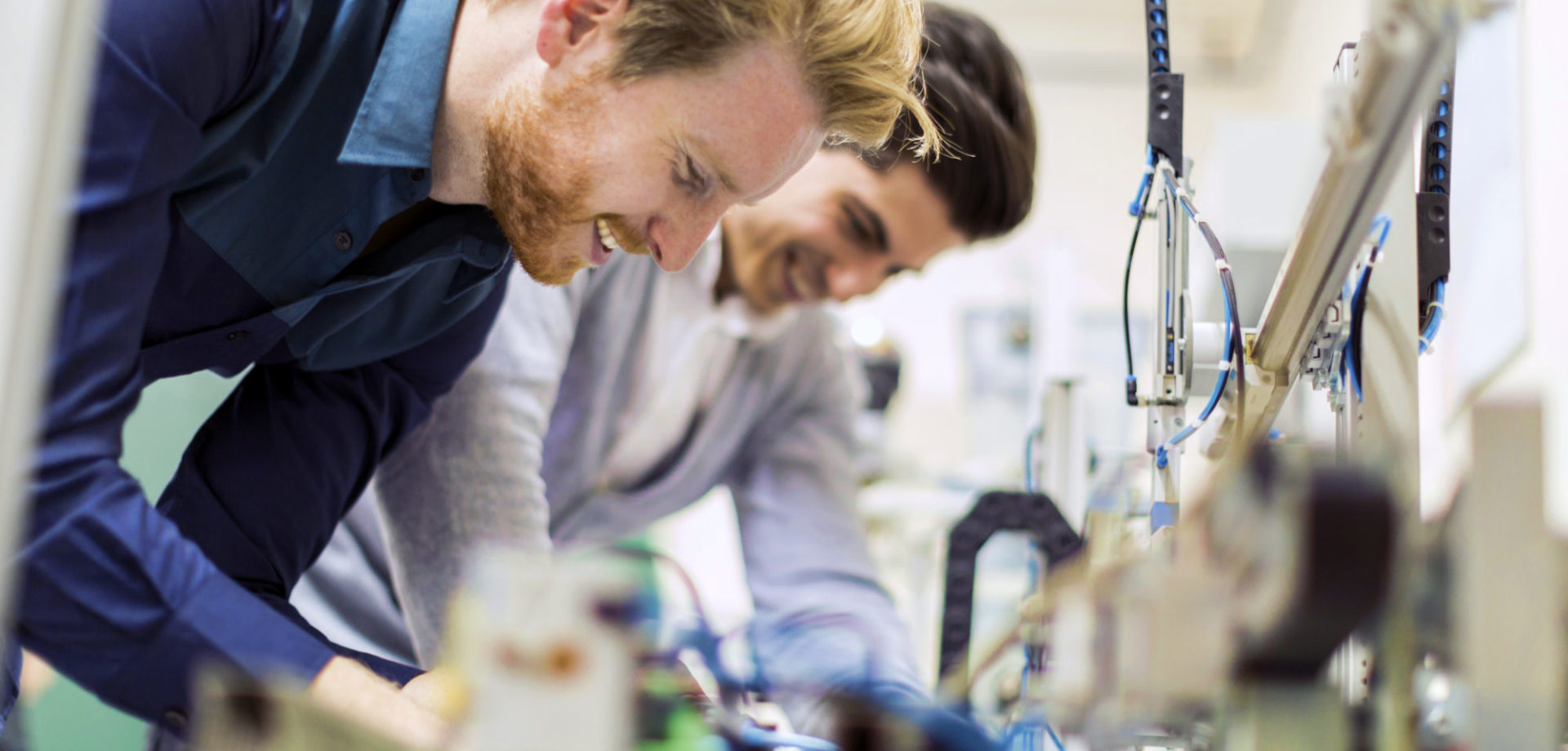 Two young handsome engineers working on electronics components and fixing broken chips